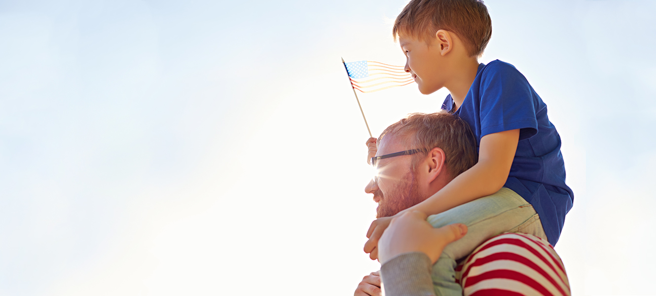Little boy on dad's shoulders waving a flag