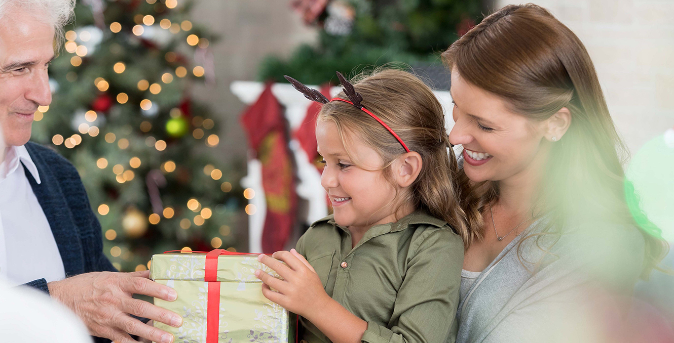 A woman holding girl with a reindeer hair bow who is receiving a present form an elderly gentleman with a Christmas tree and fireplace in the background.