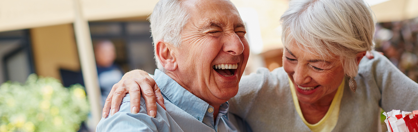 An elderly couple sitting close together laughing outdoors.