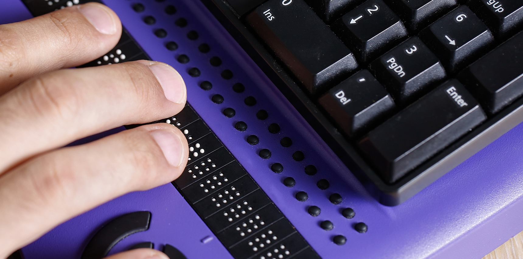 Close up of hands using a braille computer keyboard.