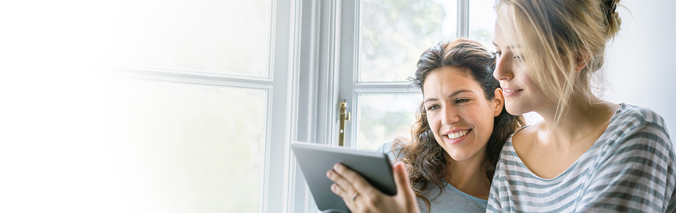Two smiling women sitting by a bay window both staring at a tablet one is holding.