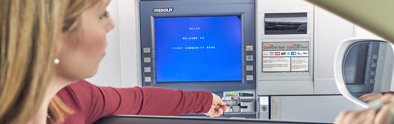 View of a woman using an ATM while sitting in her car.