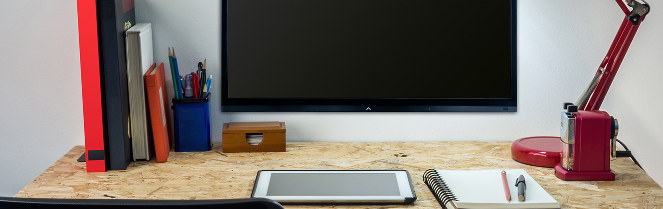 iPad laying on a desk in front of a tv screen