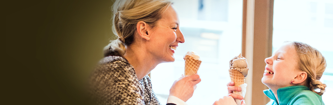 A woman and a girl sitting across from each other looking at each other both smiling eating ice cream in waffle cones.