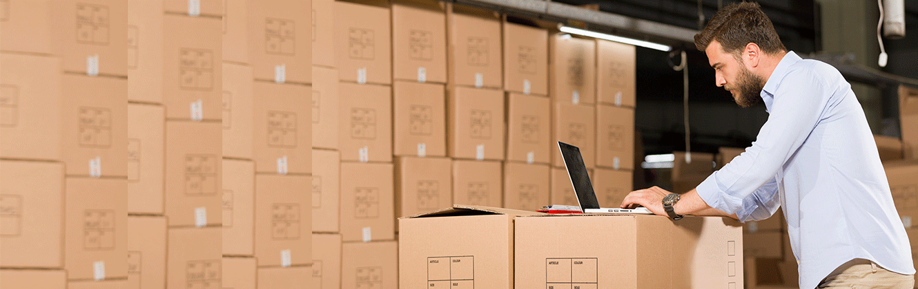 A guy standing typing on a laptop, using boxes as a desk in a warehouse full of boxes.