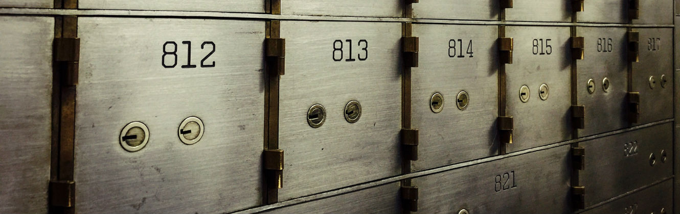 A view of grey steel safe deposit boxed, with two brass keyholes in each box.