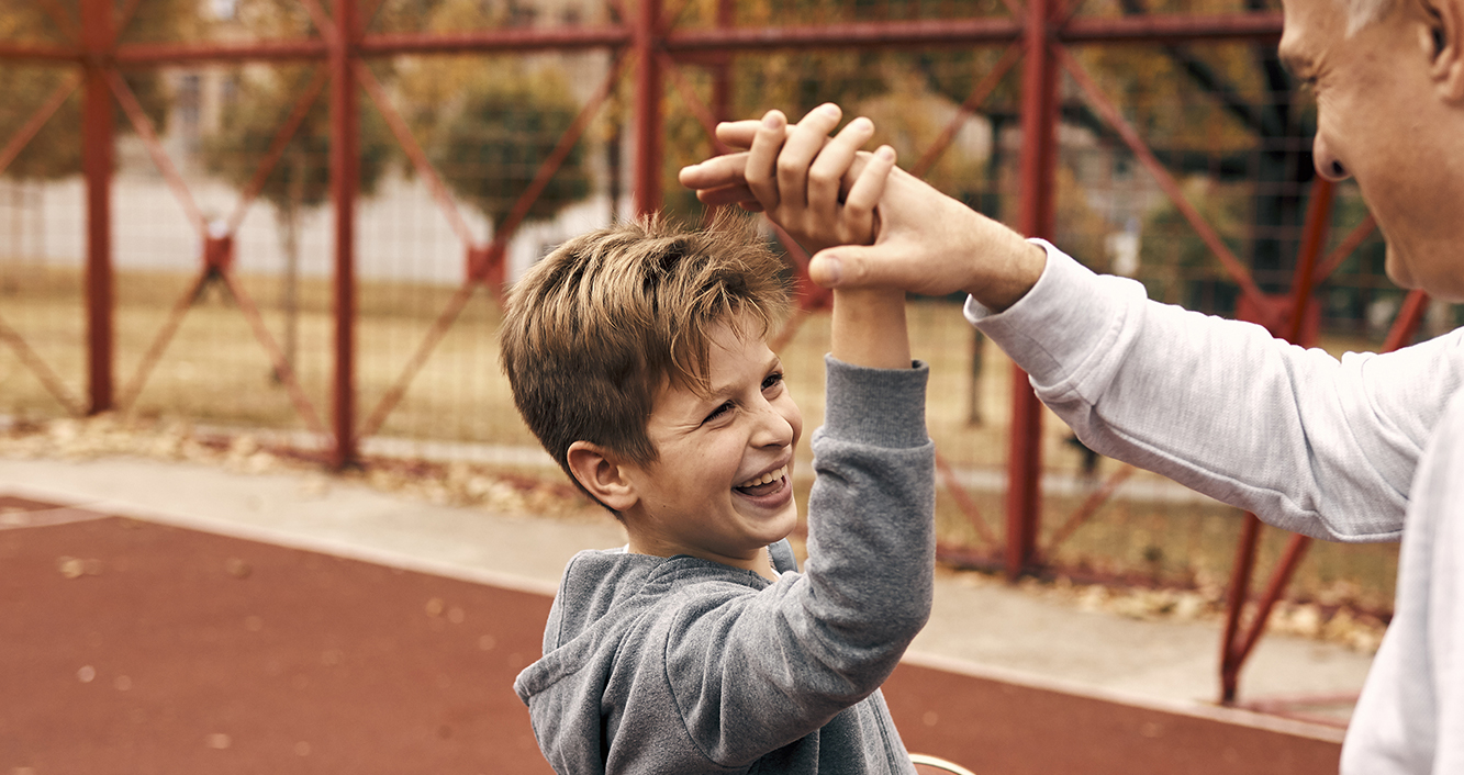 Man and child performing a high five outside on a basketball court.
