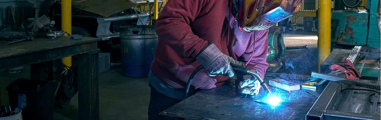 A person welding metal in a work shop.