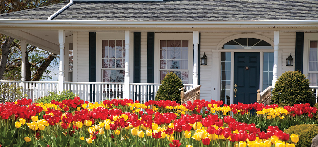 A house with a large porch with large in bloom tulips.