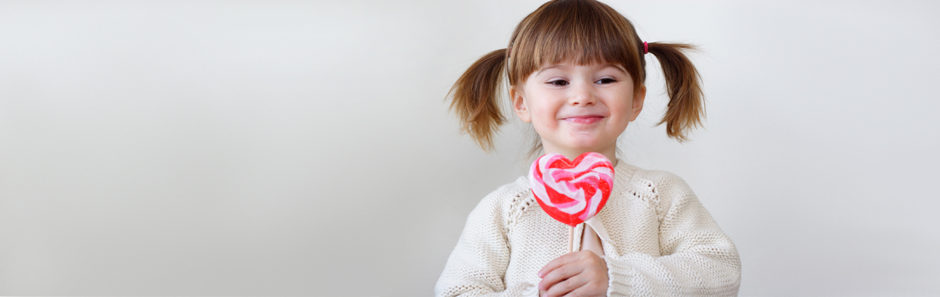 A smiling little pig-tailed girl with large heart shaped lollipop.