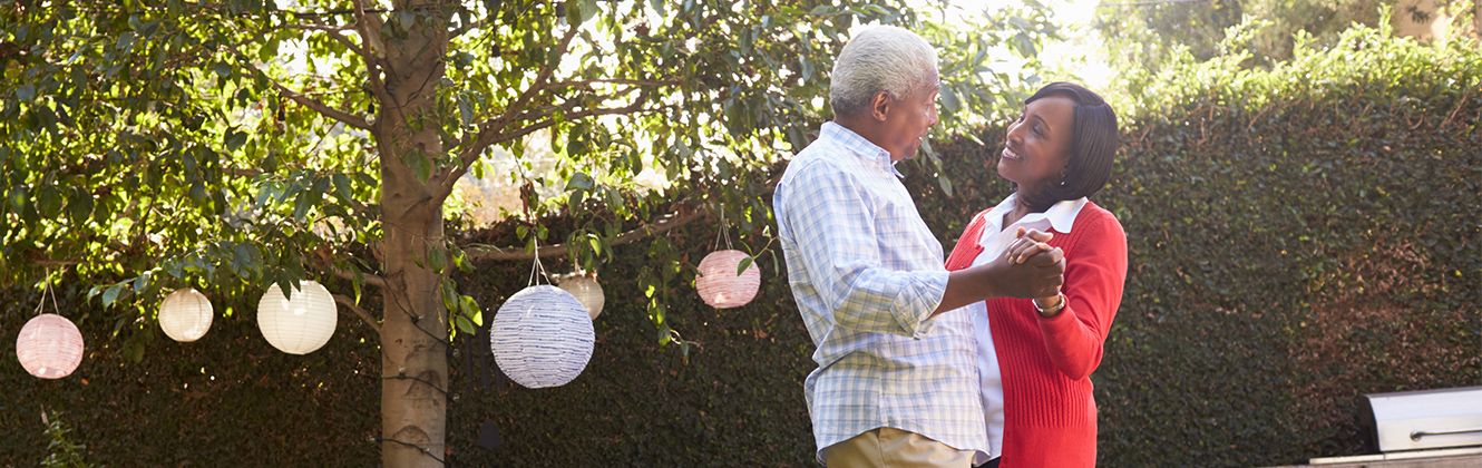 An elderly couple dancing in a back yard near a tree with paper lanterns hanging from the tree.