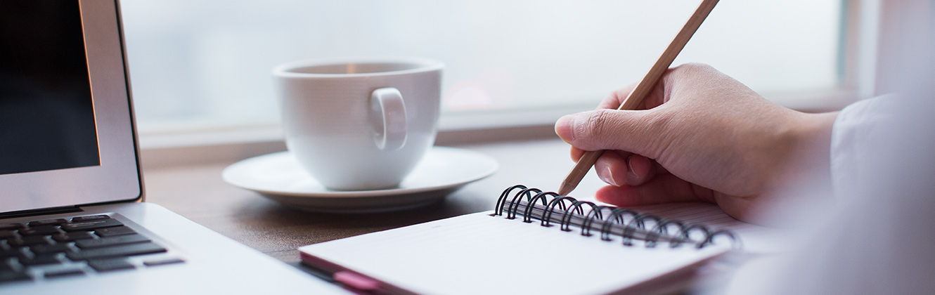 A person writing in a notebook with an open laptop and a cup and saucer.